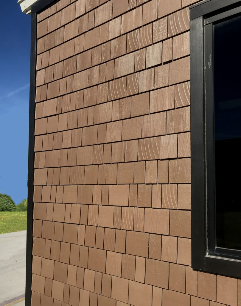 Photo of a siding product with a new multi-toned paint finish and a large range in shingle textures molded into fiber cement for a realistic look.